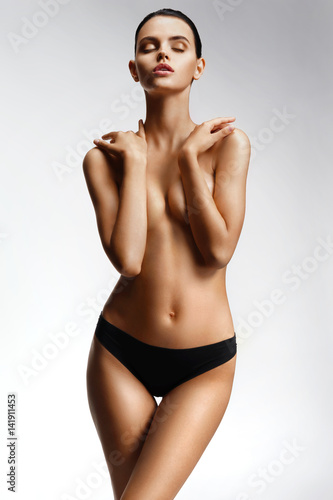 Slender girl with clean skin nude topless breasts. Beautiful girl covering her nude breast. Health and beauty concept