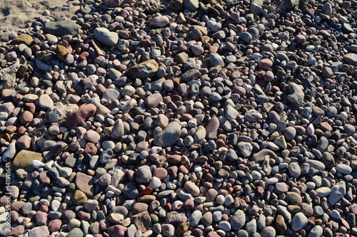 BACKGROUND of different sea stones in the sand. Poster
