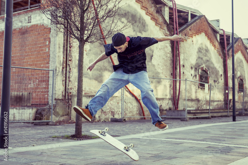 Fotobehang Skateboard young boy jumping with skateboard in outskirt street