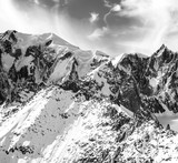 Beautiful snowy mountain peaks in North Italy and cloudscape monochrome