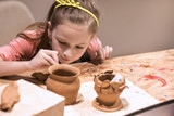 Child sculpts from clay pot. workshop on modeling on the potter's wheel.   - 141927258