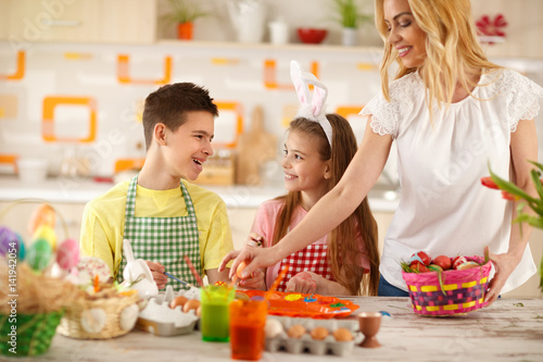 Mother putting colorful eggs in basket