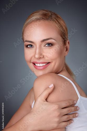 Leinwanddruck Bild woman hugging herself and laughing happily