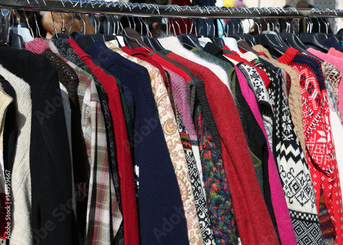 Plakat market for used clothes outdoors with many clothes