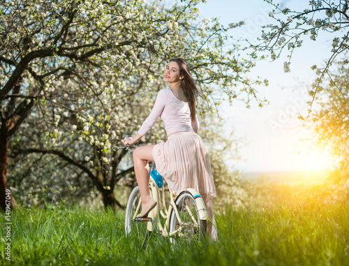 Beautiful female cyclist with retro bicycle in the spring garden Poster