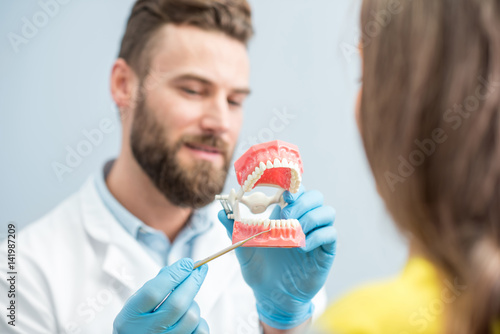 Fototapeta Handsome dentist consulting woman patient holding artificial jaw at the dental office