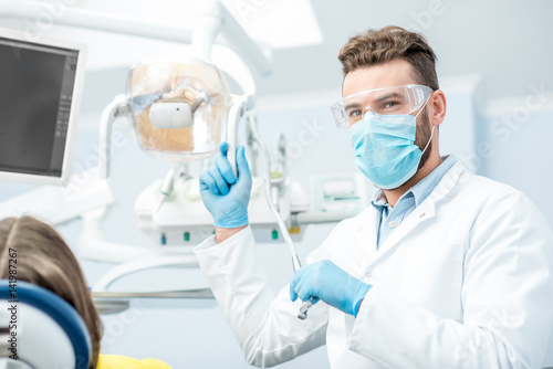 Fototapeta Portrait of a dentist in mask and protective glasses during the dental surgery