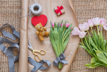 photo of beautiful pink bunches of pink tulips, cute gift, heart shaped toy, teddy bear and things for wrapping on the wonderful carpet background