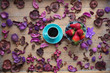 photo of cup of coffee and fresh blueberries and strawberries near wonderful dried flowers petals on the wooden background