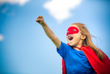 Funny little girl playing power super hero over blue sky background. Superhero concept. - 142032467