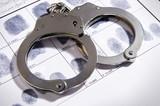 Handcuffs laying on top of fingerprint chart - 142034826