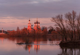 Orthodox temple on the banks of the river at sunset