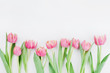 Pink tulip flowers for spring background top view in flat lay style with clean space for text. Greeting for Woman or Mother Day.
