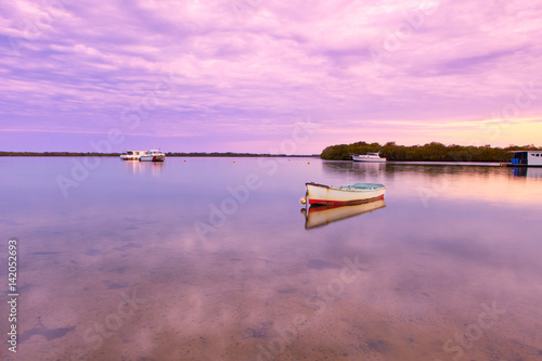Fotobehang Lichtroze A dinghy at Golden Beach in Caloundra at sunset on the Sunshine Coast in Queensland, Australia