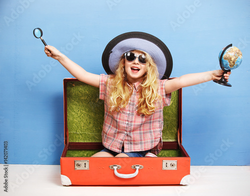 Fotografiet Happy child girl is sitting in pink suitcase holding a globe and magnifying glass