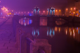 Night fog in the city. A beautiful bridge across the river. St. Petersburg. The Fontanka River and the Lomonosov Bridge.