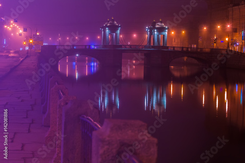 Foto op Plexiglas Violet Night fog in the city. A beautiful bridge across the river. St. Petersburg. The Fontanka River and the Lomonosov Bridge.