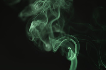 mystery wavy green smoke rising over black background