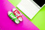colorful gumshoes and silver laptop on the wonderful colorful background in pop art style