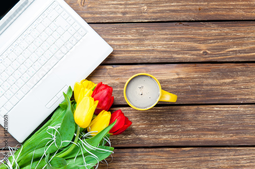 bunch of tulips, laptop and cup of coffee on the wonderful brown wooden background