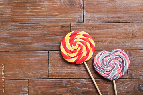 Sweet lollipops on a brown wooden table Poster