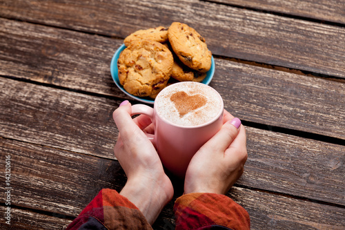 Poster female hand touching cup of coffee near plate full of cookies on the wonderful b