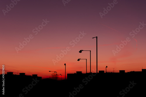Silhouette of buildings and streetlights in city before sundown Poster