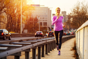 Young beautiful woman running on the sidewalk besides traffic road in the city