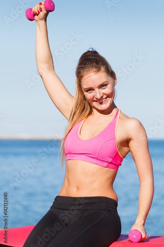 Woman doing sports outdoors with dumbbells Poster