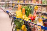Einkaufswagen voller Einkäufe in einem Supermarkt - 142142093
