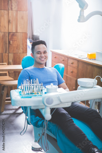 dentist talking to his patient at dental care clinic Poster