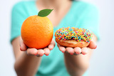 Young woman holding in hands an orange and a tasty multicolored donut, choosing healthy food or dessert - 142182806