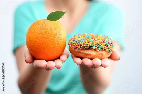 Foto Murales Young woman holding in hands an orange and a tasty multicolored donut, choosing healthy food or dessert