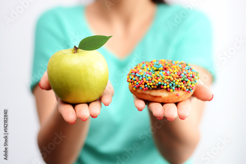 Foto Murales It's hard to choose healthy food concept, with woman hand holding an green apple and a calorie bomb donut