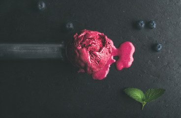 Melting scoop of blueberry ice-cream with mint leaves over black slate stone background, top view, selective focus, horizontal composition