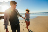 Romantic young couple holding hands and walking on beach - 142192870