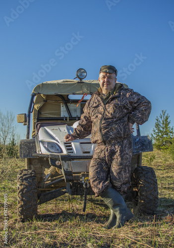 Poster Male fisherman, hunter camouflage in a suit standing next to the ATV, SUV in forest, field, summer, men's Hobbies