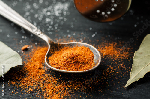 Paprika powder in metal spoon on a black wooden table