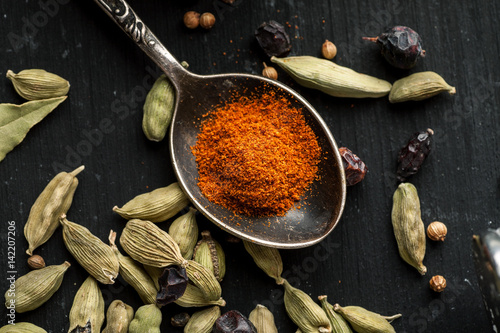 Ground paprika in a metal spoon with cardamon seeds around on a black wooden table, selective focus, top view, flat lay
