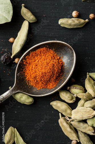 Ground paprika in a metal spoon with cardamon seeds around on a black wooden table, selective focus, vertical