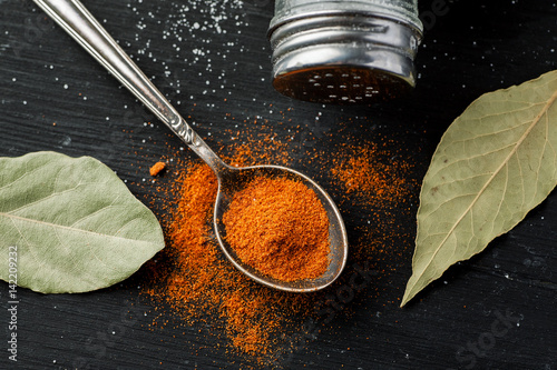 Zmielona papryka w metal łyżce i suchych bobków liściach na czarnym drewnianym stole, odgórny widok, selekcyjna ostrość