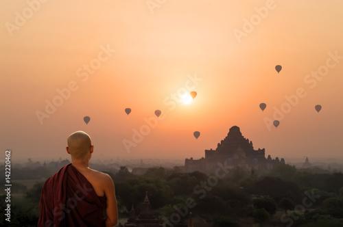 Poster Monk looking at hot air balloons at sunrise at Bagan temple in Burma, Myanmar