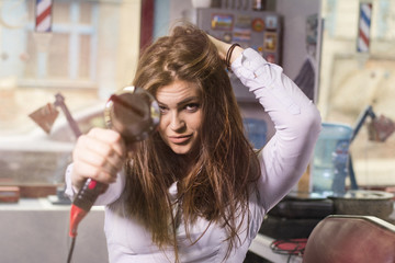 Going for a change of style. Young beautiful woman holding a hairdryer like a gun. At the hairdressers.