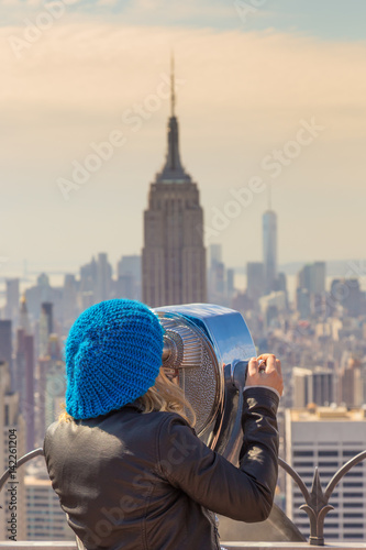 Foto op Aluminium New York Woman enjoying in New York City panoramic view. Manhattan downtown skyline with illuminated Empire State Building and skyscrapers seen from observation deck terrace.