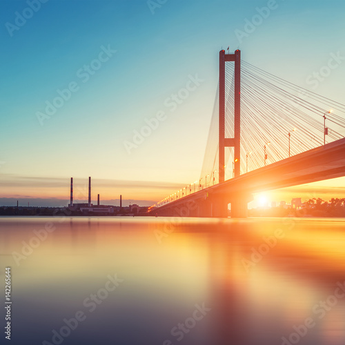 Automobile and railroad bridge in Kiev, the capital of Ukraine. Bridge at sunset across the Dnieper River. Kiev bridge against the backdrop of a beautiful sunset in Kiev. Bridge in evening sunshine