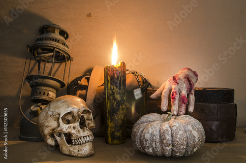 Poster Halloween image with a burning candle on an ancient skull