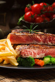 Grilled beef steak served with French fries and vegetables on a black plate.