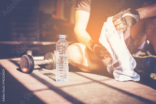 Muscular man at gym taking a break from workout sitting beside the bottle of water