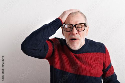 Upset senior man with headache, holding head, studio shot. Poster