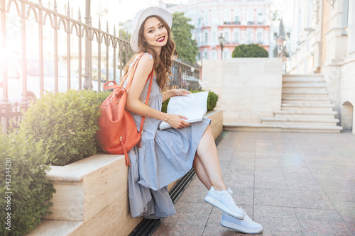 Plakat Smiling young woman sitting and reading magazine in the city